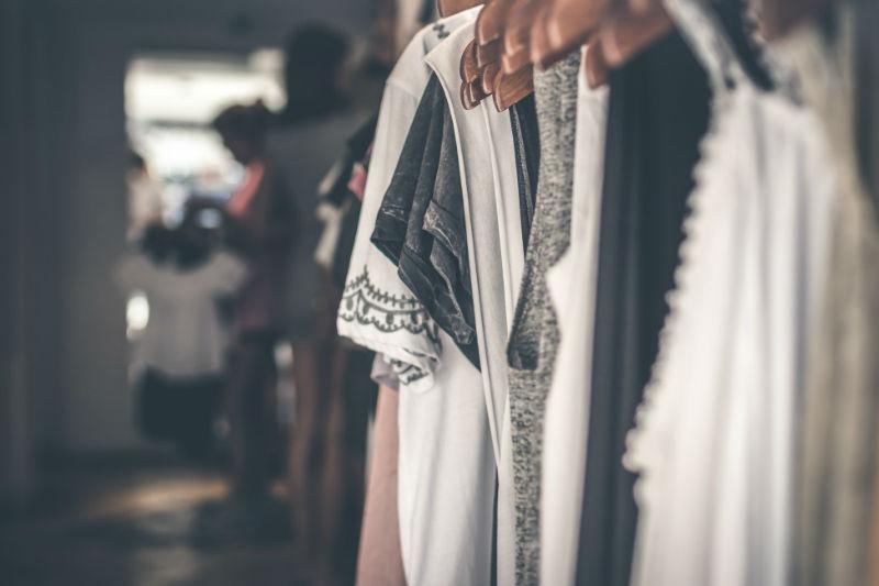 des vêtements sur des cintres en bois dans un magasin